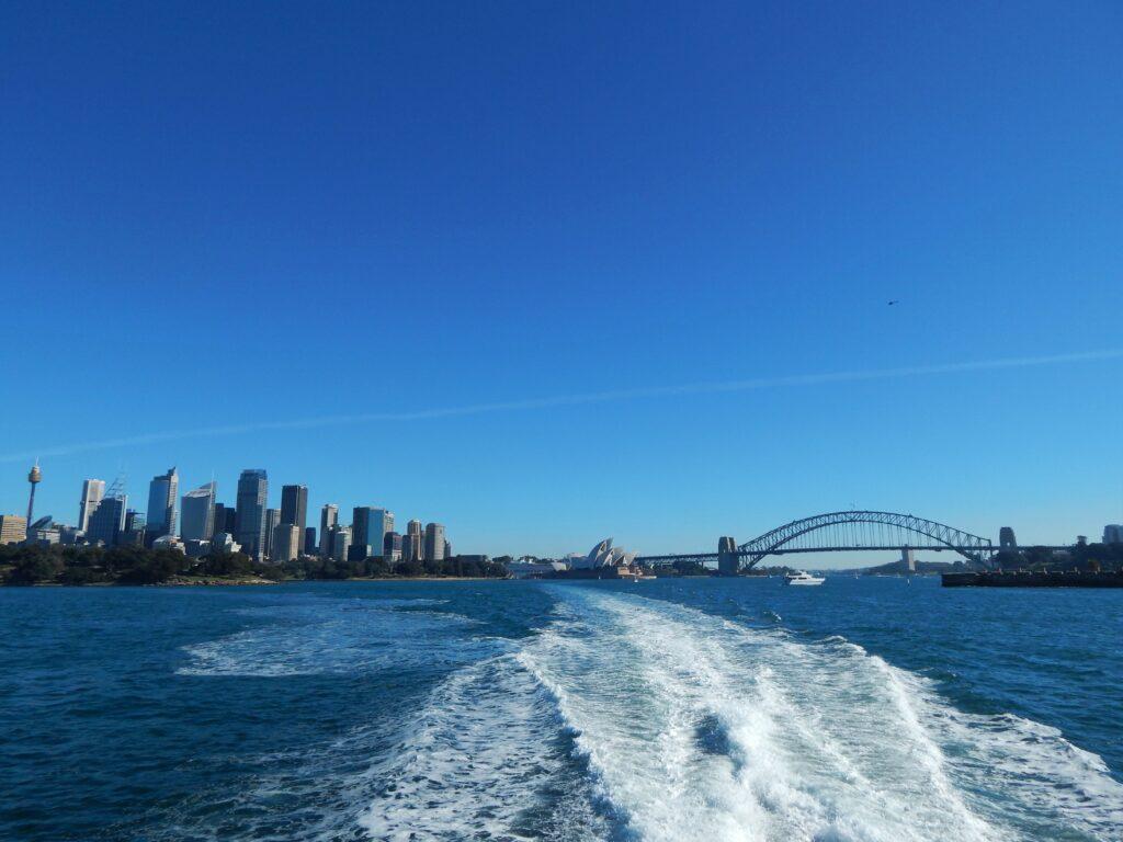 Widok na centrum Sydney, Harbour Bridge i Sydney Opera House podczas rejsu promem z Manly w słoneczny dzień