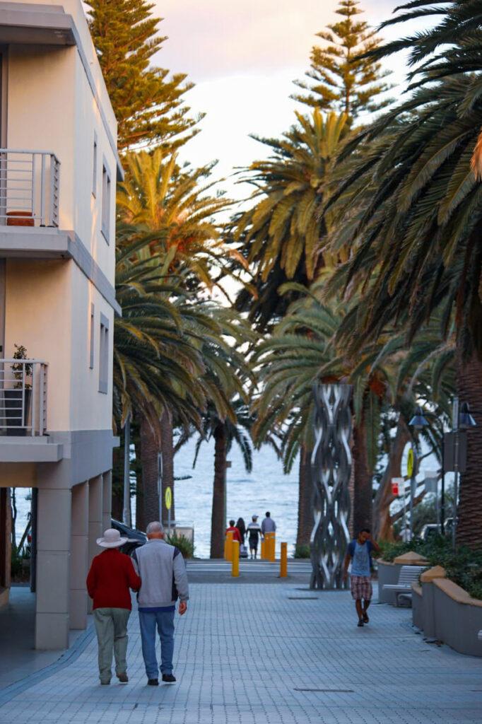 starsza para spaceruje przy plaży pod palmami